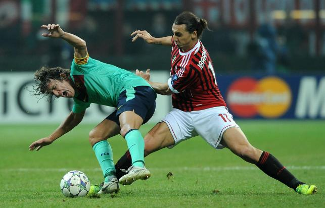 Carles Puyol i Zlatan Ibrahimović walczą o piłkę w meczu AC Milan - FC Barcelona z 23.11.2011