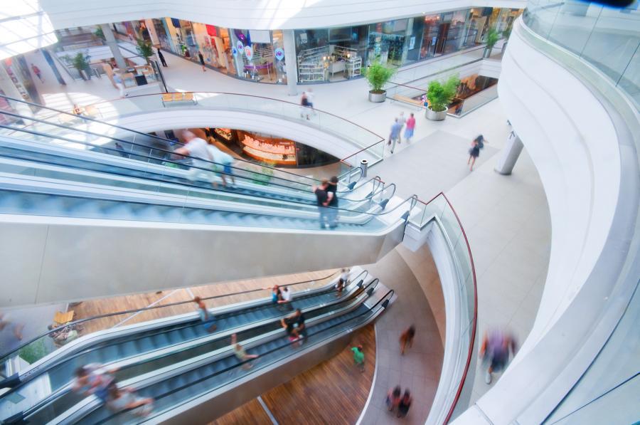 Ludzie i ruchome schody w centrum handlowym