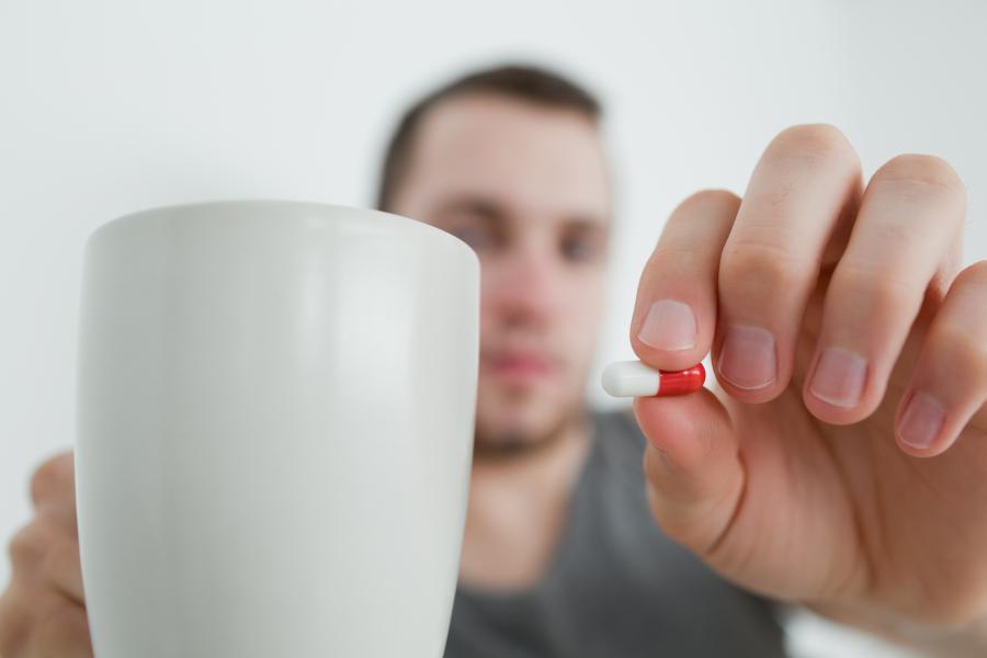 Mężczyzna zażywa lekarstwo