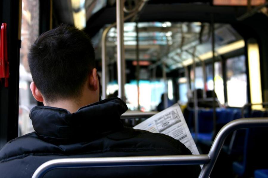 Mężczyzna czytający gazetę w autobusie