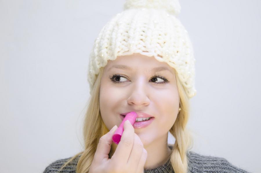 Kobieta malująca usta pomadką ochronną