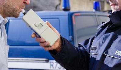 Policjant badający kierowcę alkomatem