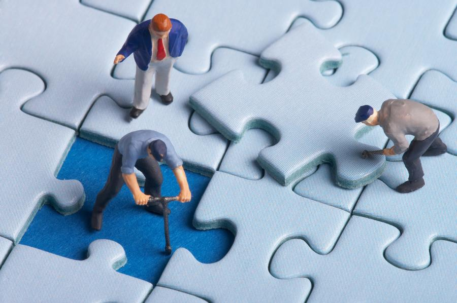 Figurki pracowników łatających puzzle
