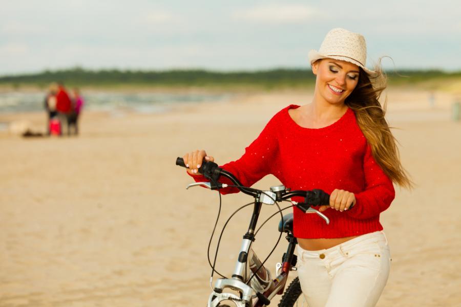 Kobieta z rowerem na plaży
