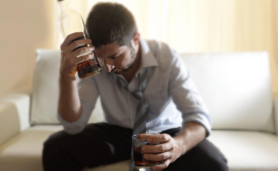 Mężczyzna samotnie pije alkohol
