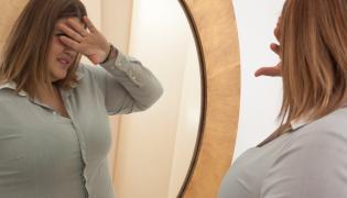 Puszysta kobieta przed lustrem